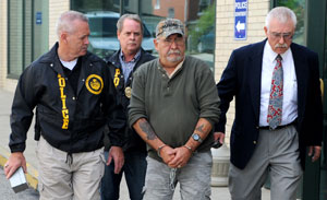 Corrections Officer Harry Nicoletti is escorted out of the Dormont Municipal Building in 2011.