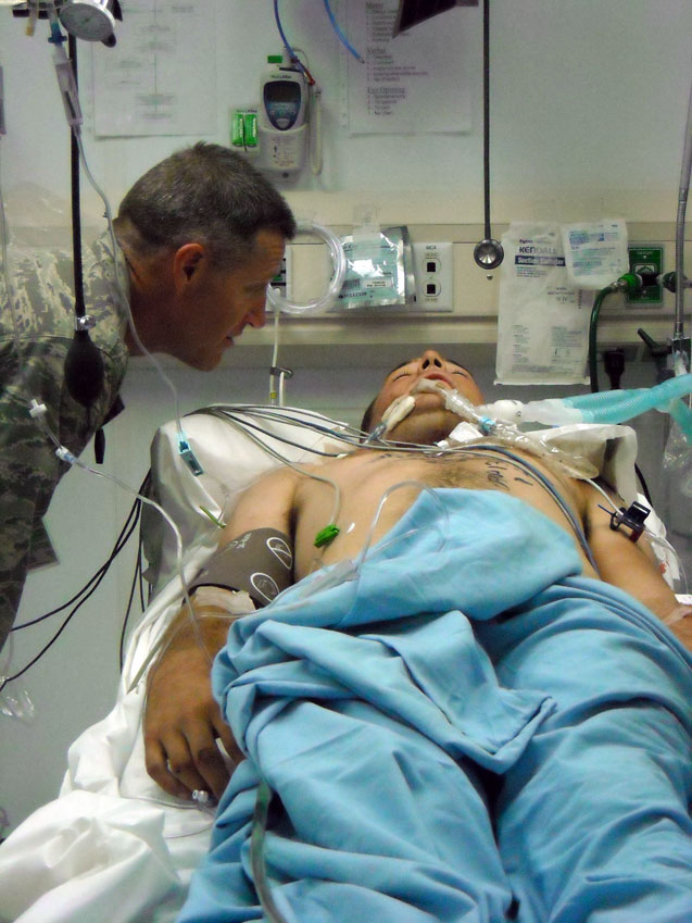 Chaplain Air Force Reserve Major Brad Davis offering comfort to a soldier who has been shot in the neck.