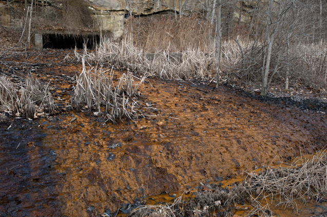 Acid mine drainage pours out of an abandoned mine near Dunkard Creek in Greene County, Pa.