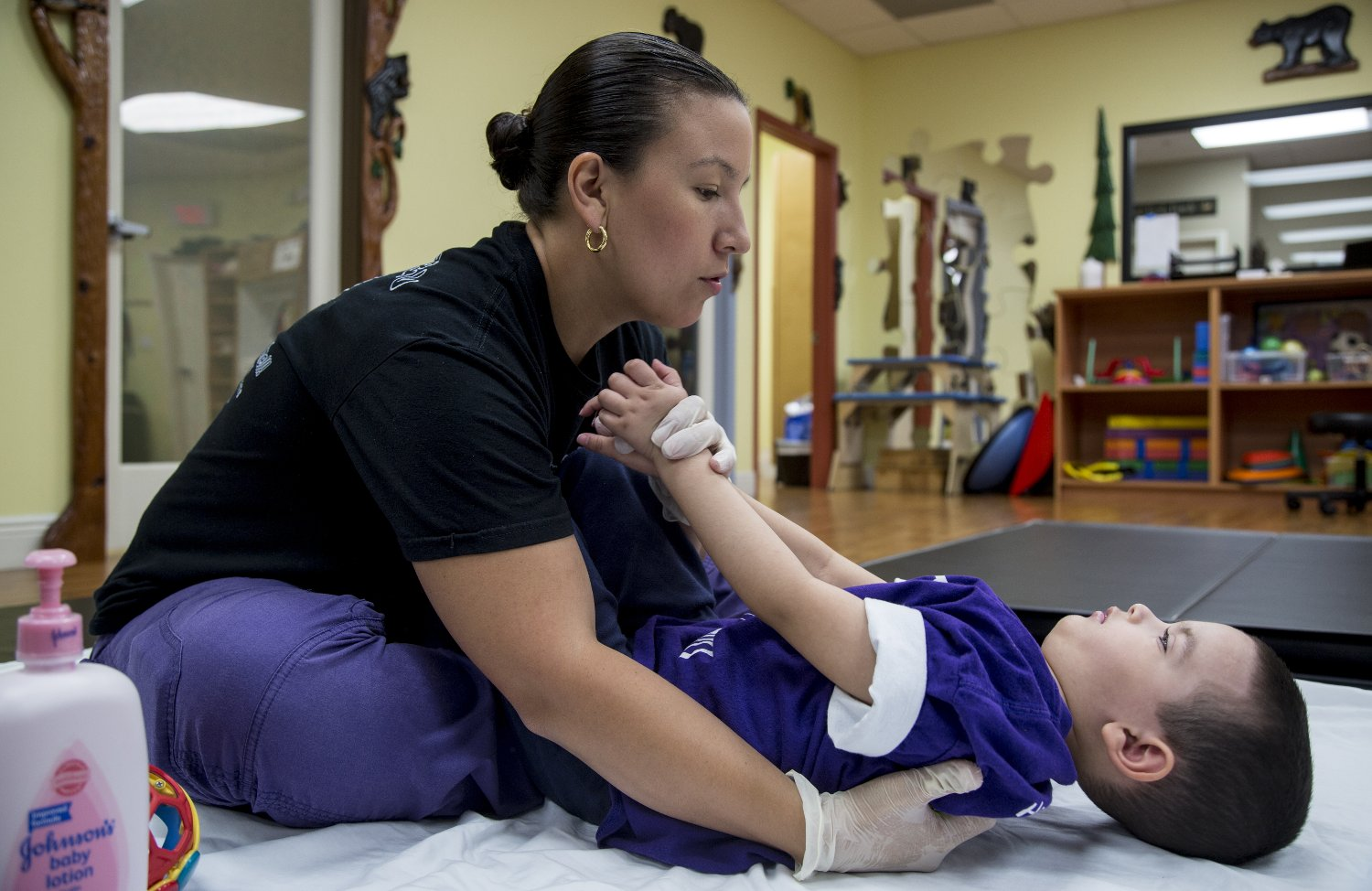 Physical therapist Cynthia Espinal excercises Bruno Stillo, 4, at B&V Thera-Pro in Miami, Florida.