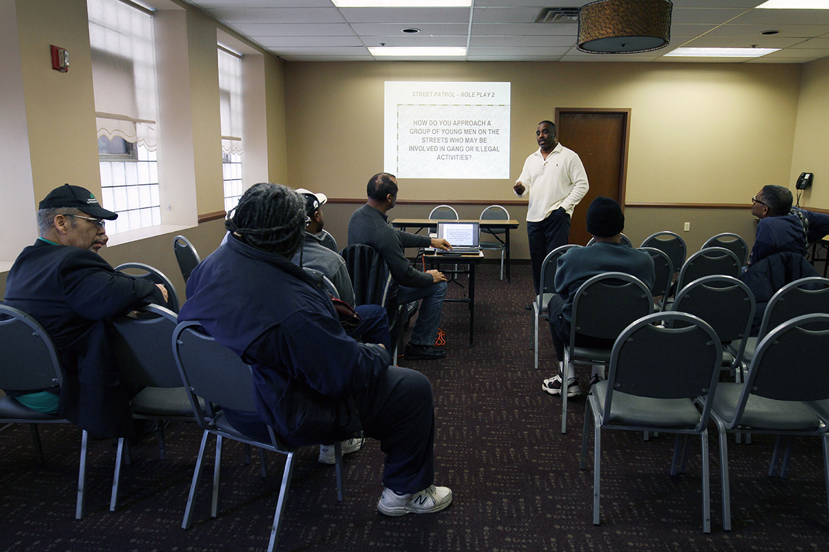Donald Giddens, patrol director for the Greater Pittsburgh Area MAD DADS, leads a training session with group members on a recent Saturday at Hosanna House in Wilkinsburg. (Photo by Ryan Loew/PublicSource)