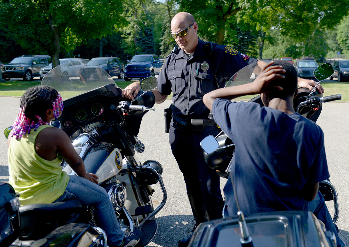 Pittsburgh City patrolman Kevin Carey talks with children while letting them sit on the police motorcycles at the Zone 5 community open house at the station on May 28, 2015. (Photo by Pam Panchak/Post-Gazette)