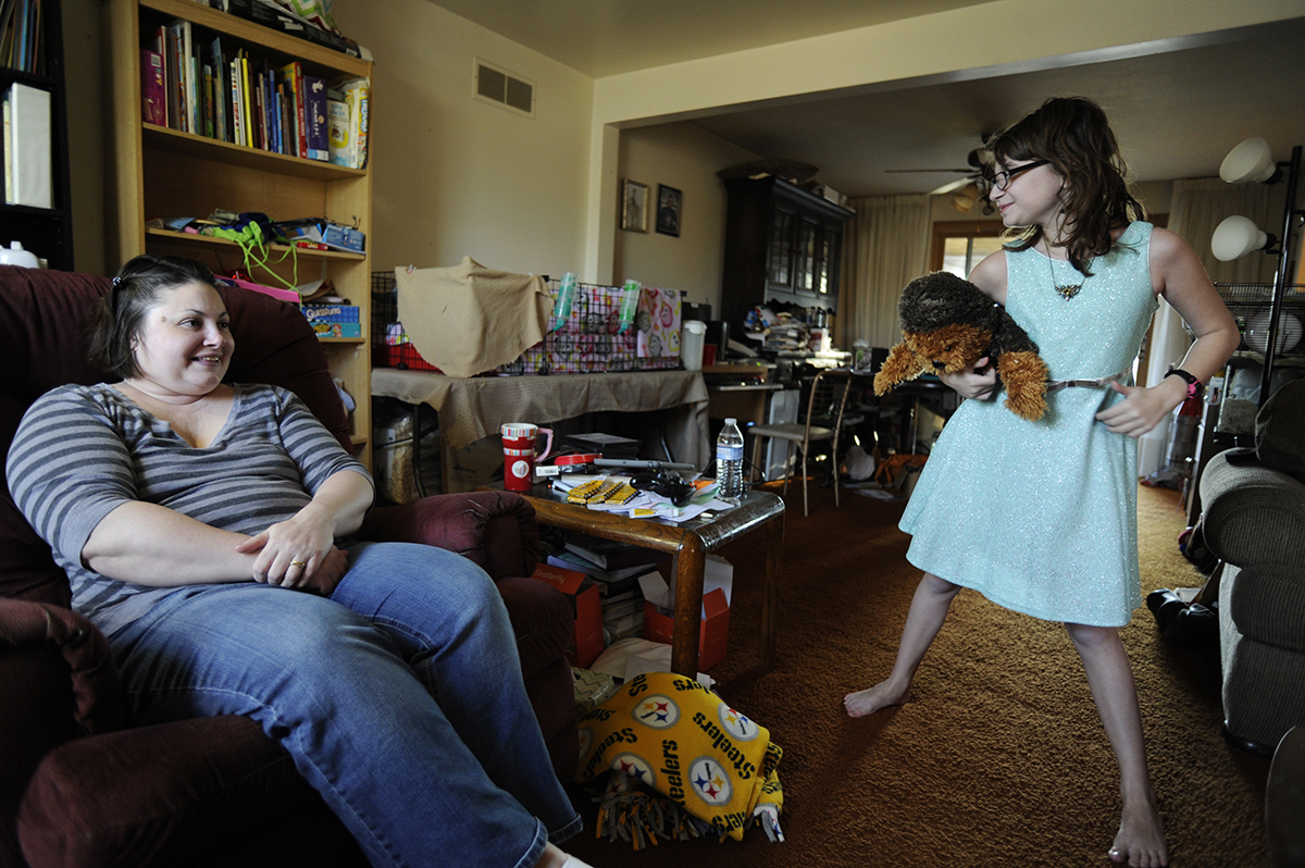 Angel Vogel watches her daughter, Lucy, play in their Baldwin home. Vogel had difficulty breastfeeding Lucy, who is now 11 years old, but she was able to breastfeed her younger son, Sam, with guidance from La Leche League. (Photo by Connor Mulvaney/PublicSource)
