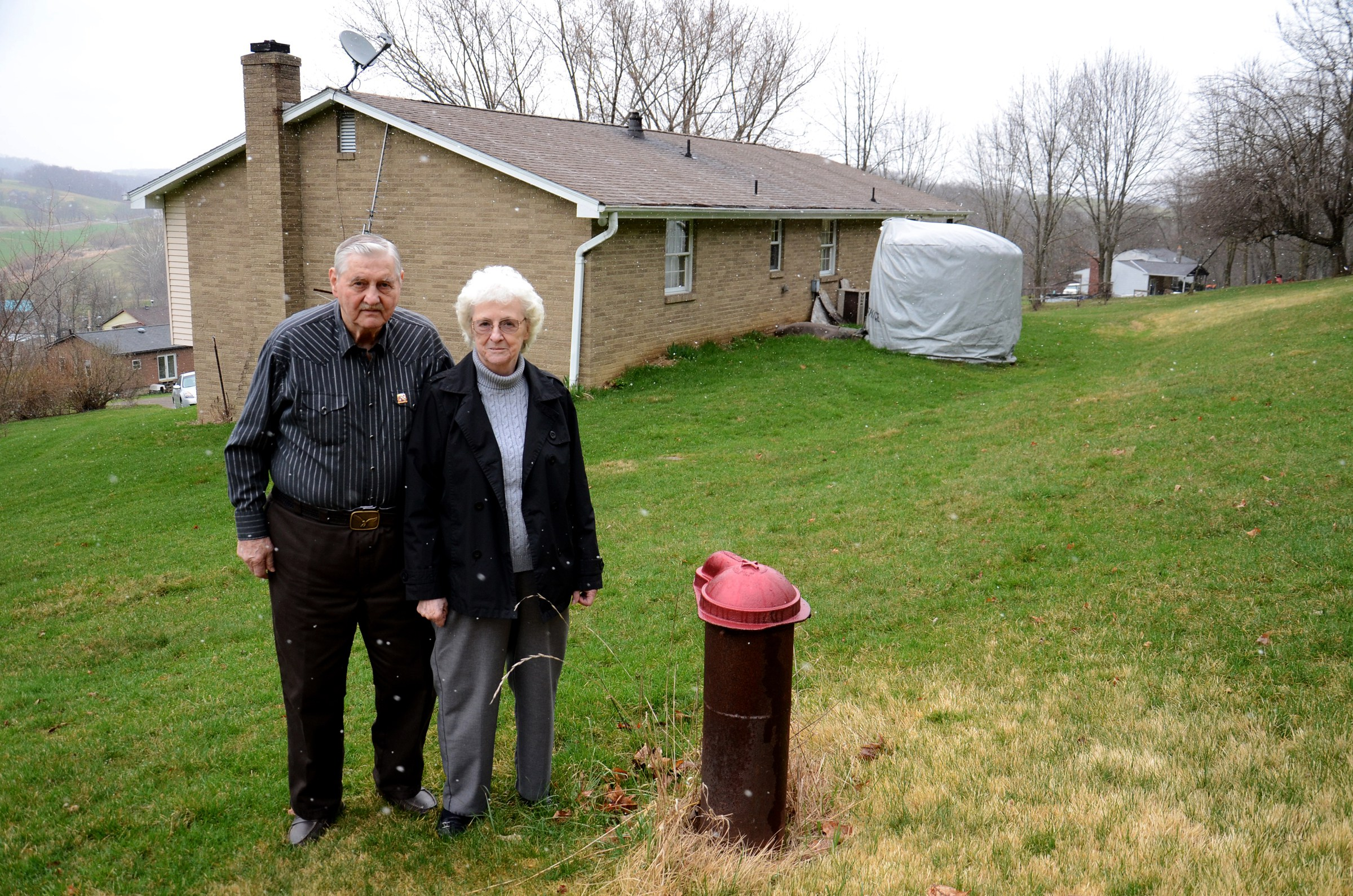Jesse and Shirley Eakin stand by the water well they no longer use at their home in Avella, Pennsylvania. Delivered water is stored in the tank behind them. (Maryam Jameel / Center for Public Integrity)