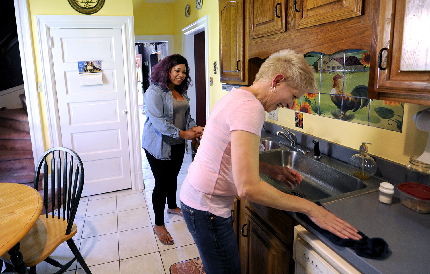 Tristan Haggerty and her adoptive mother, Kimberly Mavilla, chat and clean up the kitchen in the Bellevue house that has become a permanent home for the teenager. (Photo by Connor Mulvaney/PublicSource)
