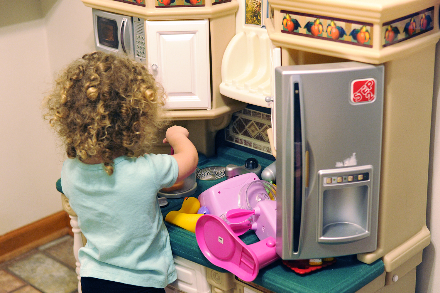 Michael Coblenz's 3-year-old daughter, Rebecca, plays with a toy kitchen set in their Squirrel Hill home. The Coblenz family recently replaced their lead water pipes. (Photo by Connor Mulvaney/PublicSource)