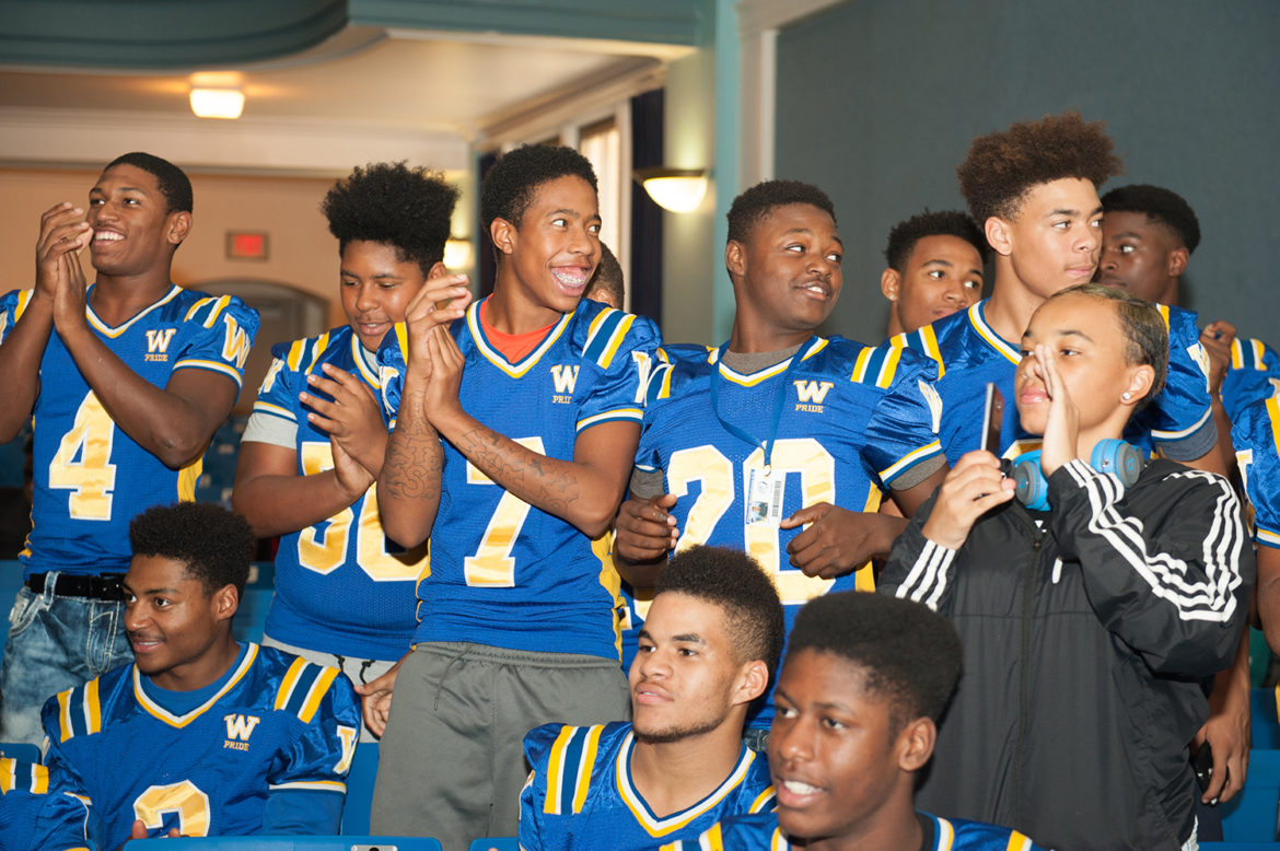 The Westinghouse Academy football team cheers for the alumni being honored at the Wall of Fame induction at the high school on Oct. 5. (Photo by Sarah Collins/PublicSource)
