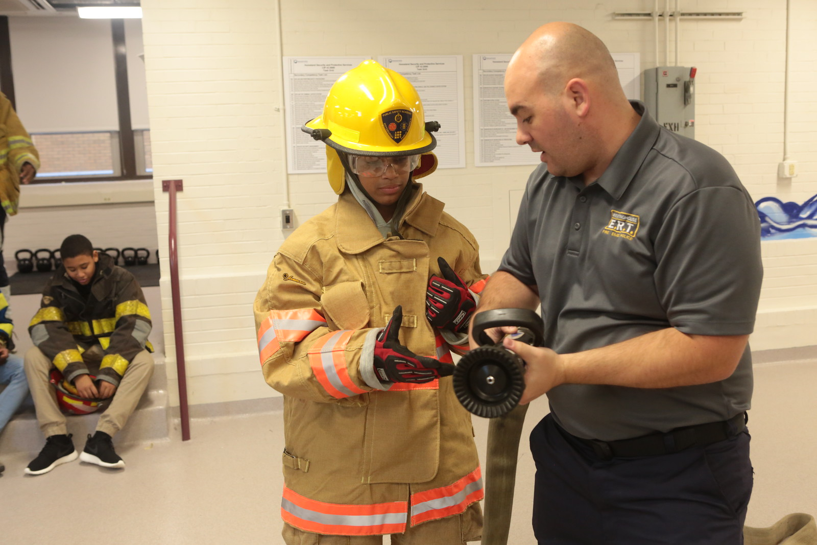 Matthew S. Patrick, the instructor of the Emergency Response Technology program, explains to a student how to use a fire hose. (Photo by Brian Cook/PublicSource)
