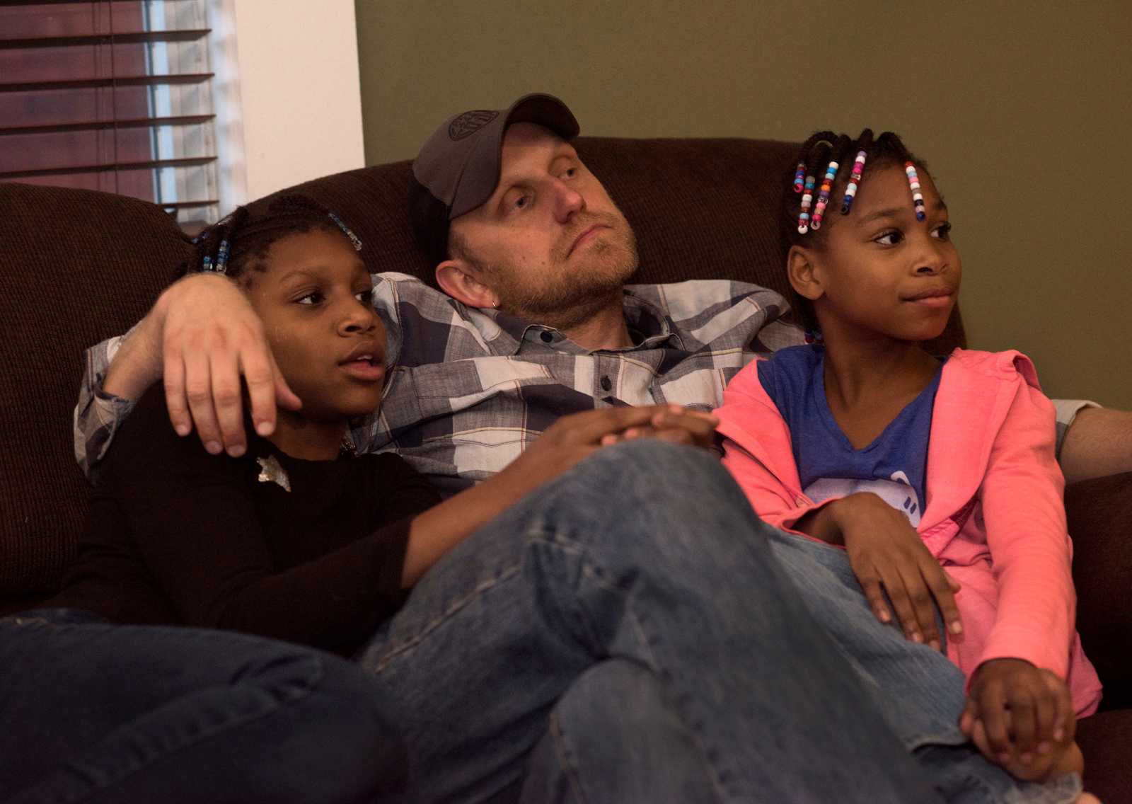 Carria (left) and 10-year-old Akeelah (right) cuddle with their father, John Rooke, following a family dinner at their Observatory Hill home. Christi and John Rooke have adopted seven children. (Photo by Martha Rial/PublicSource)