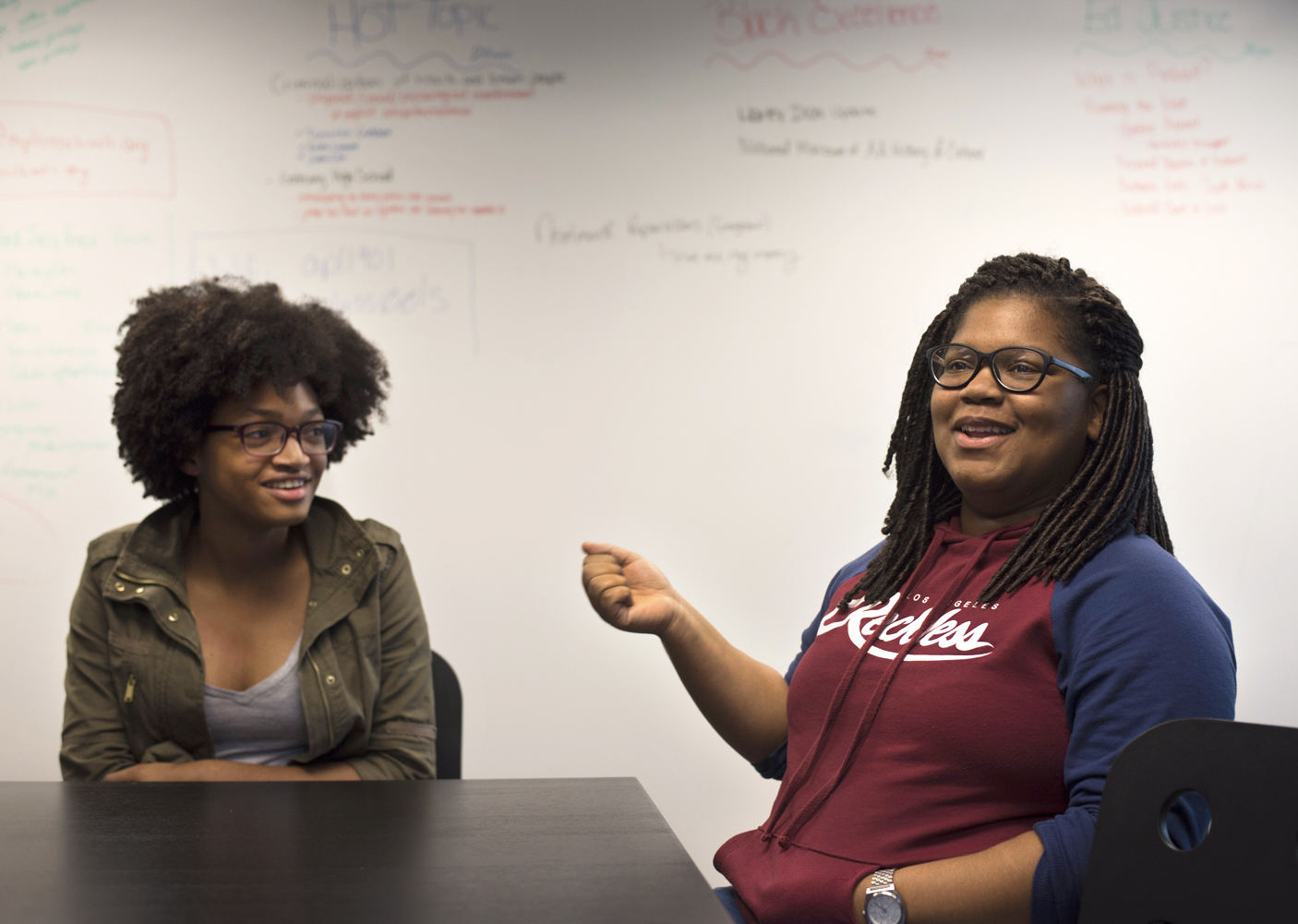 Ahmari Anthony, a senior at Shady Side Academy, shares her experiences as a young black woman in Pittsburgh with Kelis Campbell, a junior at Obama Academy, during a TeenBloc meeting at A+ Schools in the Hill District. (Photo by Martha Rial/PublicSource)