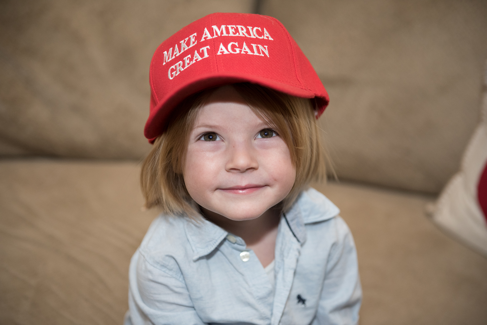 "Micah Brockett, 4, tries on his mother's ""Make America Great Again"" hat. His mom, Kristin Koltick, sported the hat at Trump rallies to show her support. (Photo by Sarah Collins/PublicSource)"