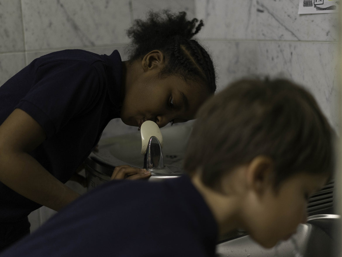 La'Shaya Lineburg (left) and Isaac Lott, students at the Environmental Charter School at Frick Park, take a drink from the school's water fountains. The school voluntarily tested all of its drinking and cooking water fixtures and plans to replace the few that showed lead levels, even though they are below the EPA's school guidelines. (Photo by Aaron Warnick/PublicSource)