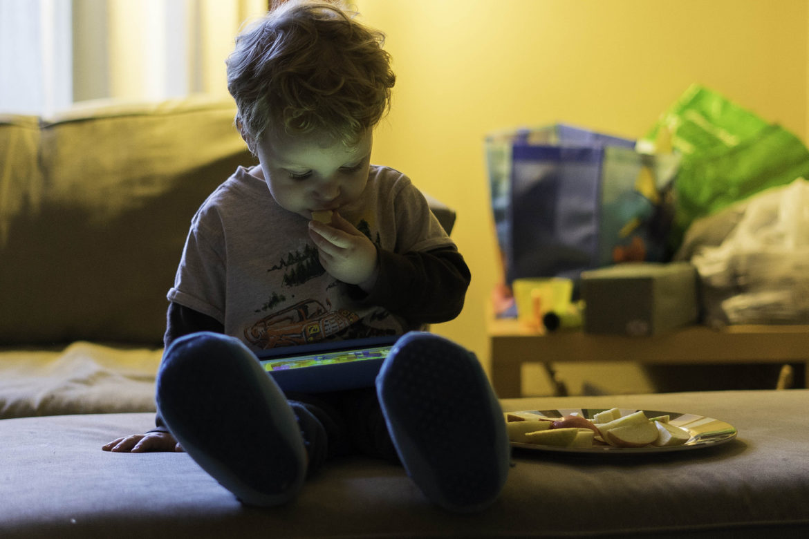 "Oren Lev, 2, snacks on an apple during his allotted ""screen time"" at the family's Point Breeze home. When he was 1, a pediatrician detected lead in his blood. (Photo by Aaron Warnick/PublicSource)"