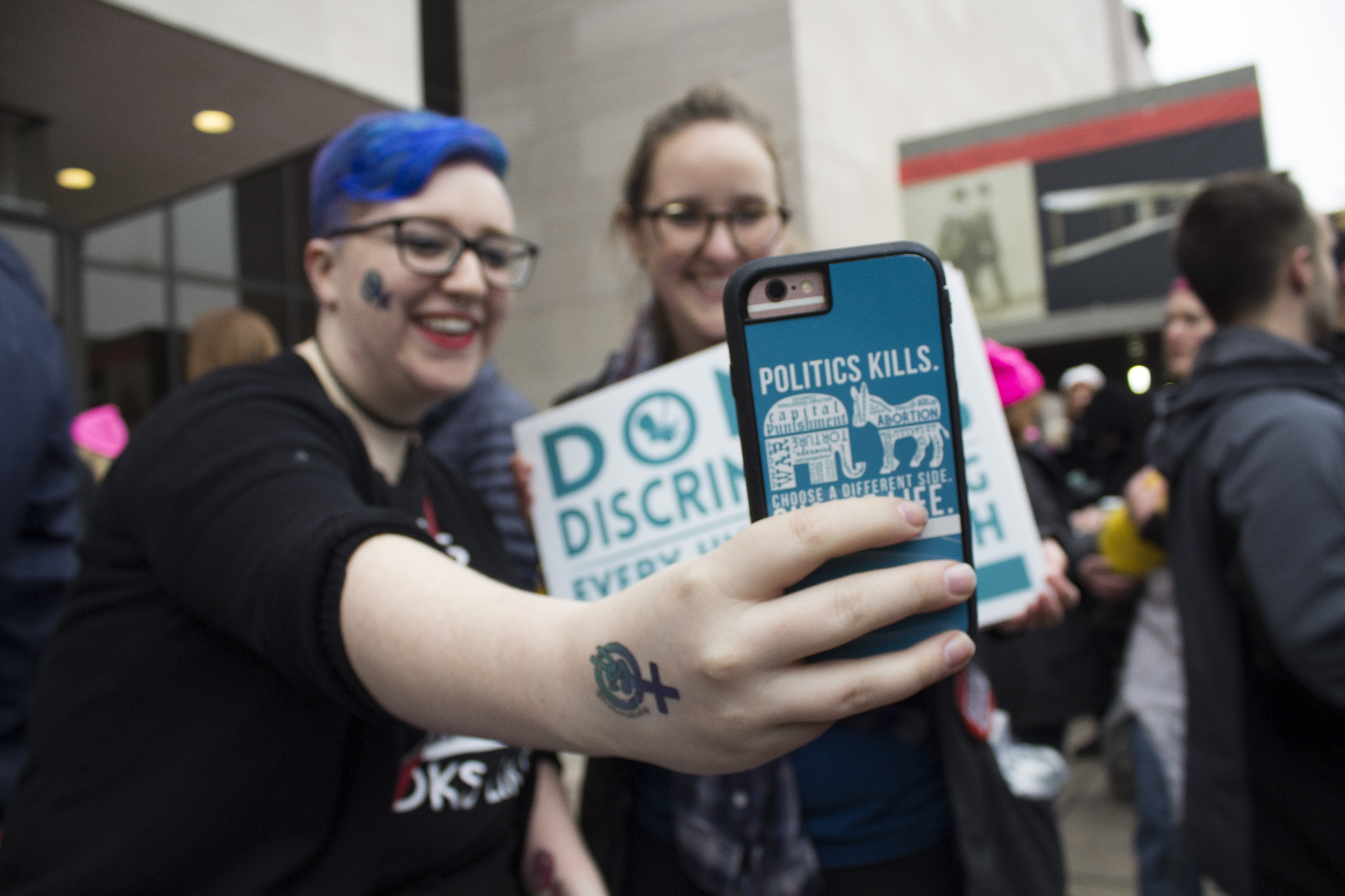 "Rosemary Geraghty snaps a selfie with her friend outside the Air and Space Museum at the Women's March on Washington. Geraghty's phone case reads, ""Politics Kills."" (Photo by Molly Duerig for PublicSource)"
