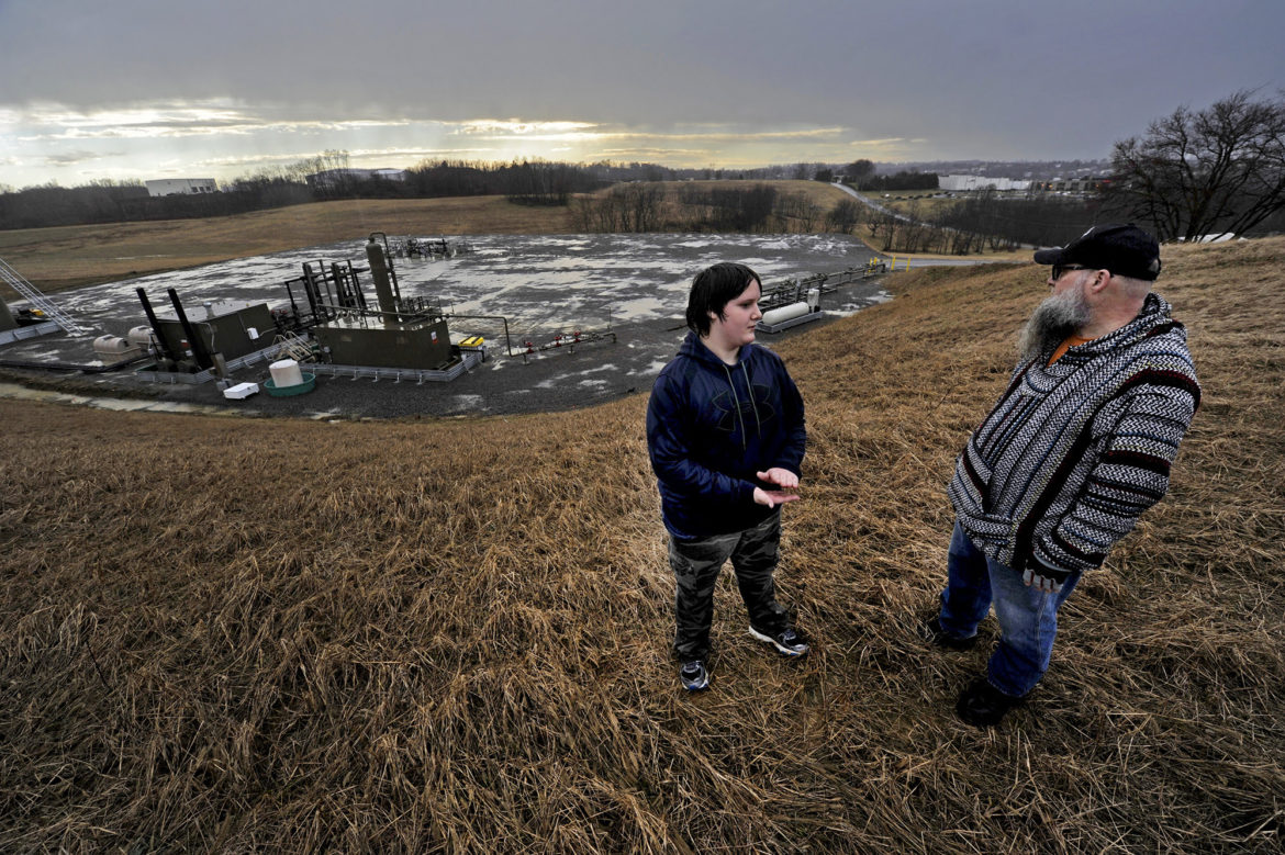 James Moore and his 15-year-old son Chakotay, stand in front of Apex Energy's Quest well pad in Penn Township in February 2016. The father and son are the closest people living to the shale wells, just 500 feet away, and participated in PublicSource's air quality monitoring project. (Photo by Connor Mulvaney/PublicSource)