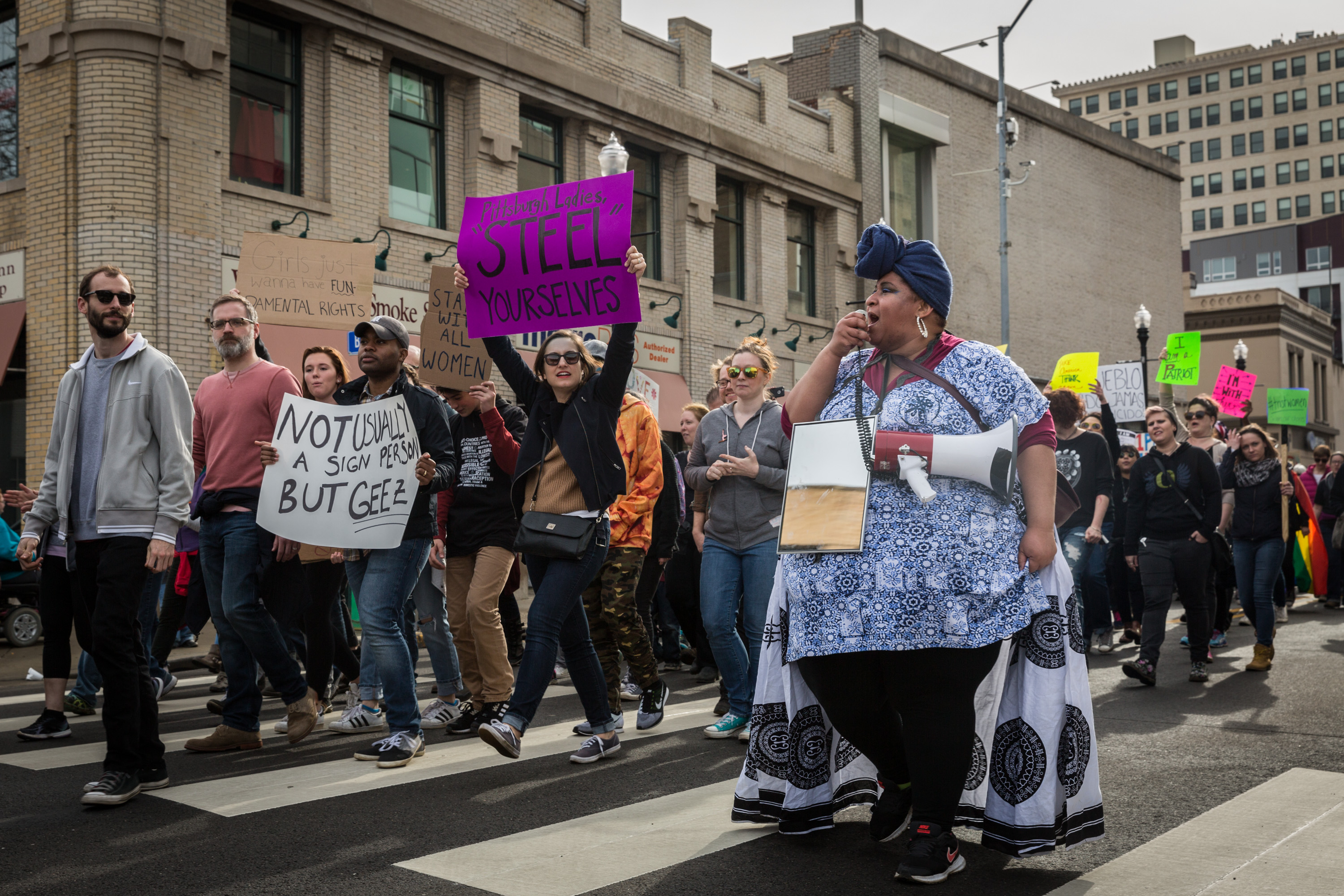 Celeste Scott, one of the organizers for the Women's March held in East Liberty, leads the crowd of over 1,000 on Highland Ave. Saturday, January 21, 2017.More than 1,000 people turned out to support the intersectional march held in East Liberty on Saturday, January, 21, 2017. The march was created in response to what the organizers called a lack of diversity and inclusion in the organization of the Women's March being held Downtown Pittsburgh at the same time. (Photo by Maranie Staab for PublicSource)