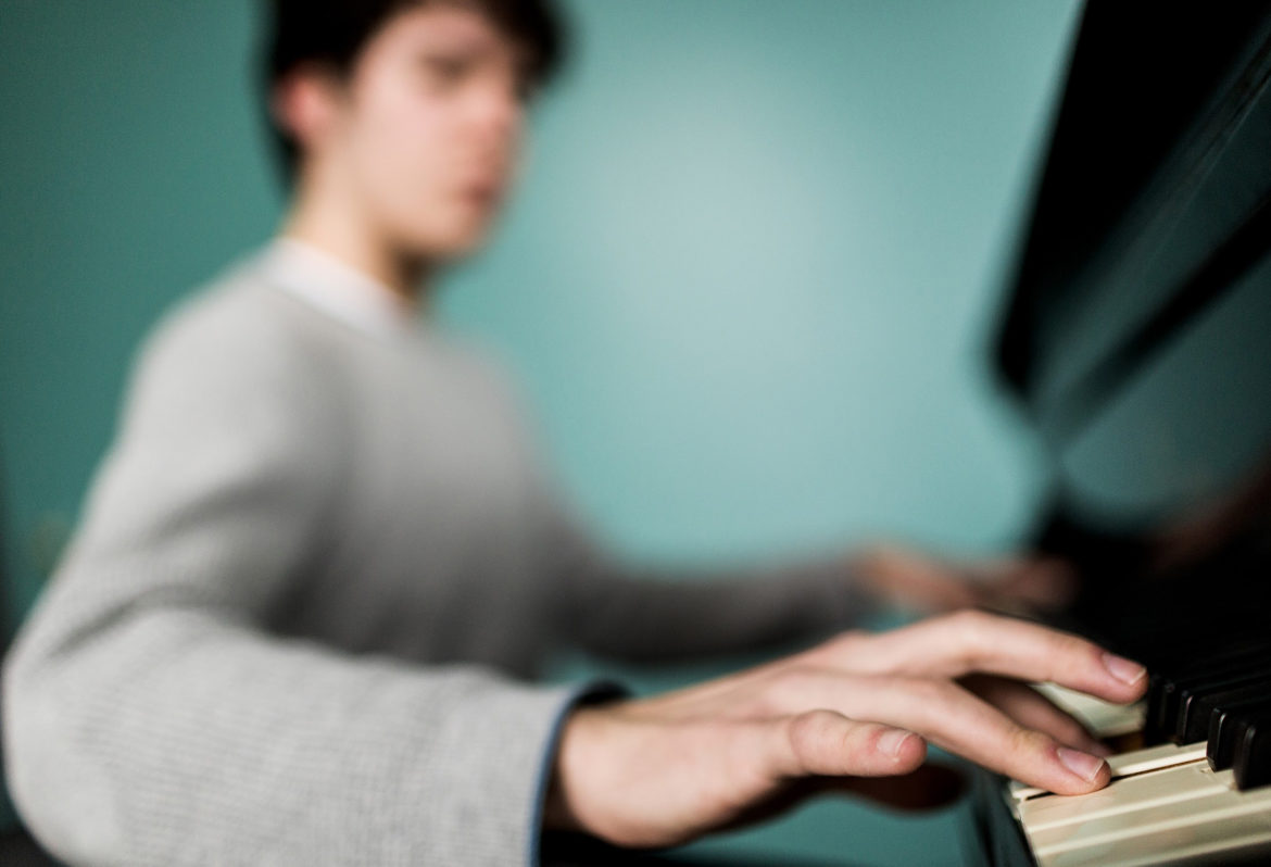 "Michael, a freshman at Dartmouth College, plays piano in a student center on the New Hampshire campus. One of the resources he has found the most rewarding is the college's faculty of professional piano instructors. ""I started playing piano this past term and ...it's something I really, really, enjoy,"" he wrote in an email. (Photo by Robert C Strong II/PublicSource)"