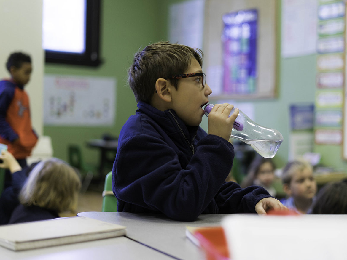 Environmental Charter School student Tyler Hurst drinks from a bottled water that contains a filter. (Photo by Aaron Warnick/PublicSource)