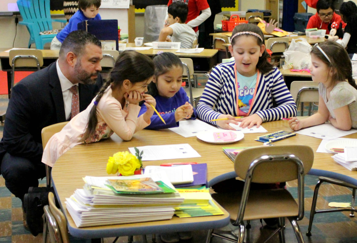 PA secretary of education pedro rivera sitting with students.