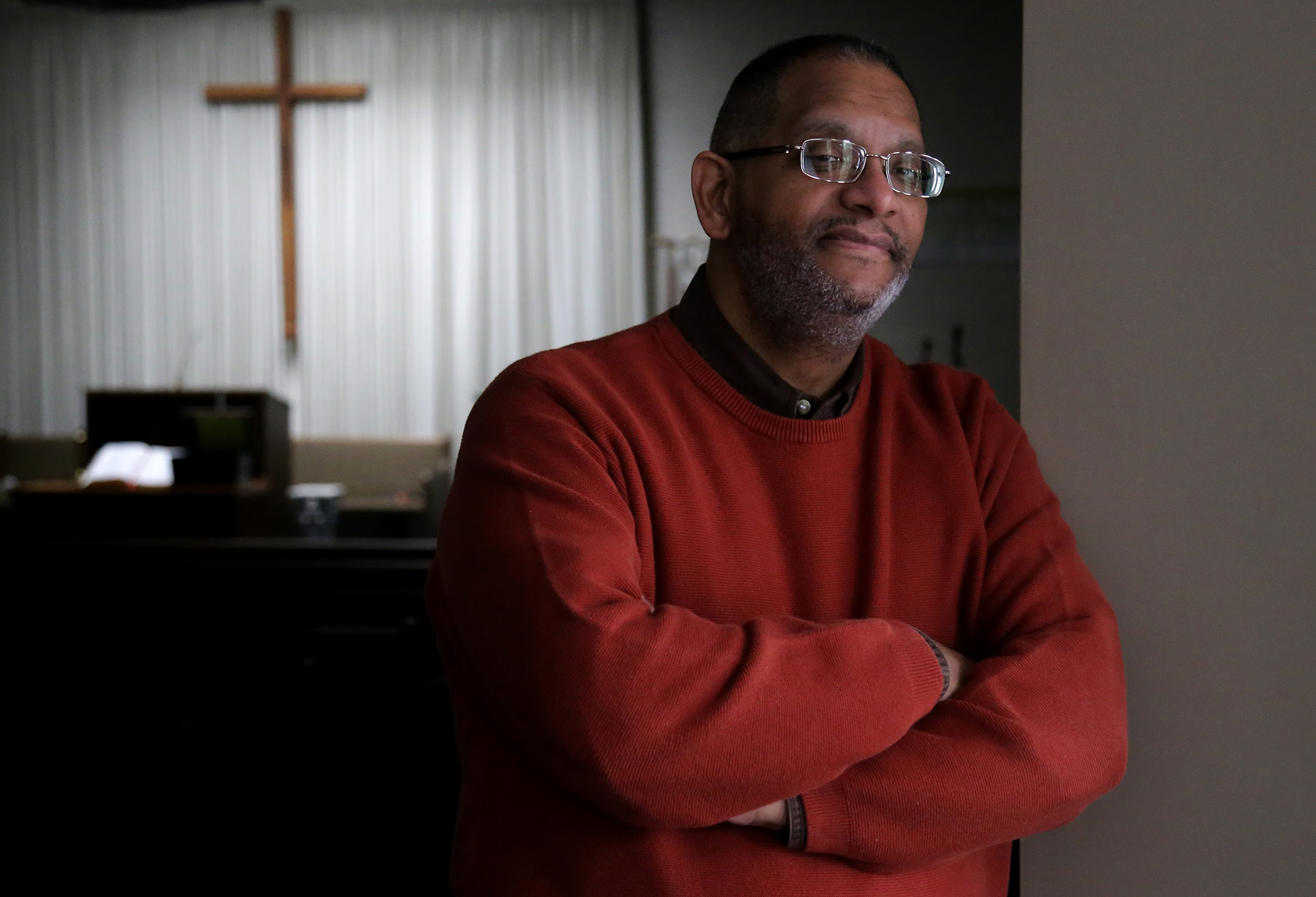 pastor in red sweater standing in church with cross behind him