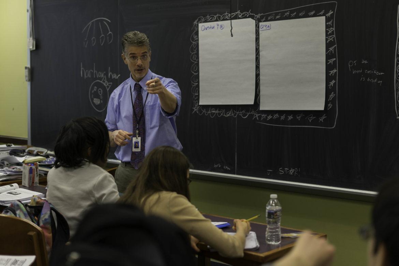 teacher at head of classroom instructing students