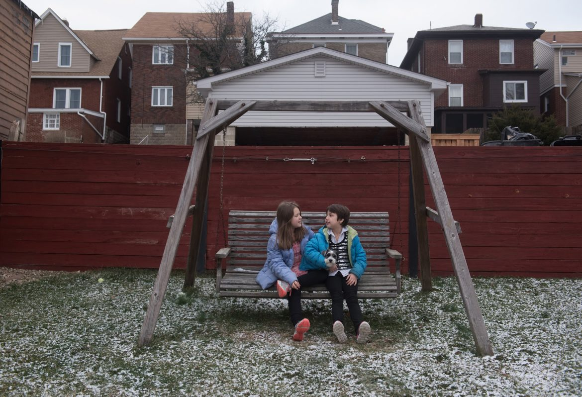 Sabrina Snyder, 9, right, sits on a backyard swing with her 10-year-old sister, Gabby, at their Brookline home on Jan. 30, 2017. (Photo by Justin Merriman/PublicSource)