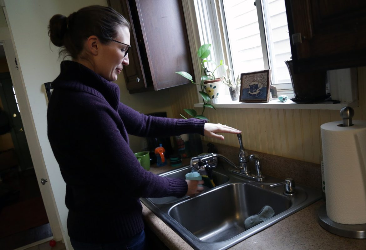 Bridget Urda, 33, fills a cup of filtered water for her son Clayton. Urda said she and her husband, Nick, use filters in their kitchen and bathroom sinks. They're also careful to use filtered water for cooking and brushing teeth, as well as in the humidifier in Clayton's bedroom. (Photo by Ryan Loew/PublicSource)