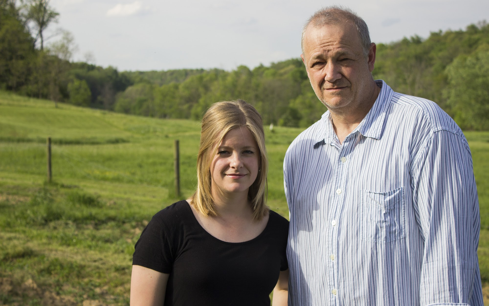 Sarah Rebitch, 26, and her father Ed Rebitch, 58, stand on their 150-acre property in Salem Township, located just outside of Delmont Borough. (Photo by Molly Duerig/PublicSource)