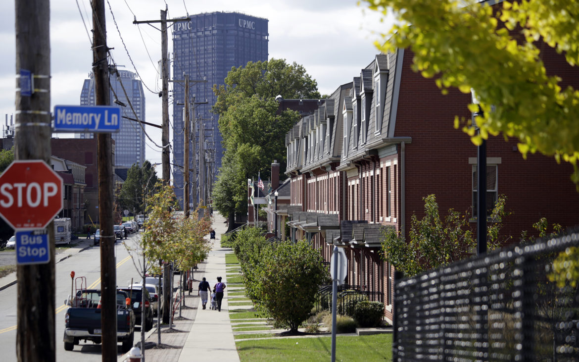 People walk along Bedford Avenue near the Bedford Hill Apartments in Pittsburgh's Hill District. The Housing Authority of the City of Pittsburgh is trying to secure more low-income housing in the city. (Photo by Ryan Loew/PublicSource)