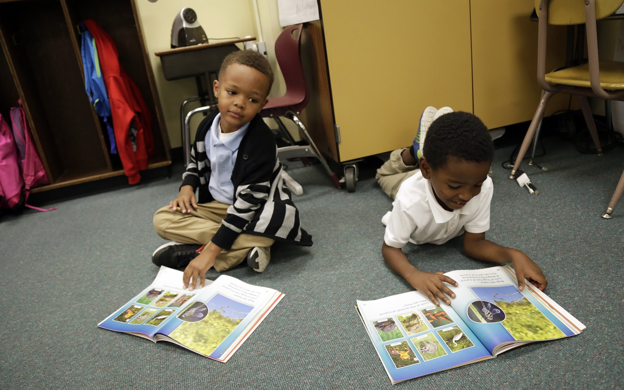 Barrett Elementary School first grade students Eion Cook, 6, (left) and Christian Page, 6, partner read books about animal habitats on Nov. 1, 2017. (Photo by Ryan Loew/PublicSource)