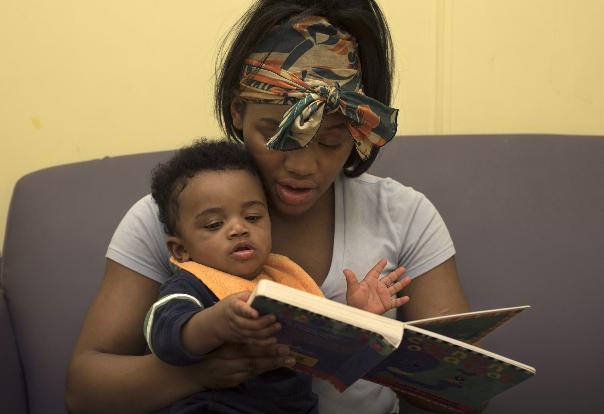 Tyneisha reads to her son