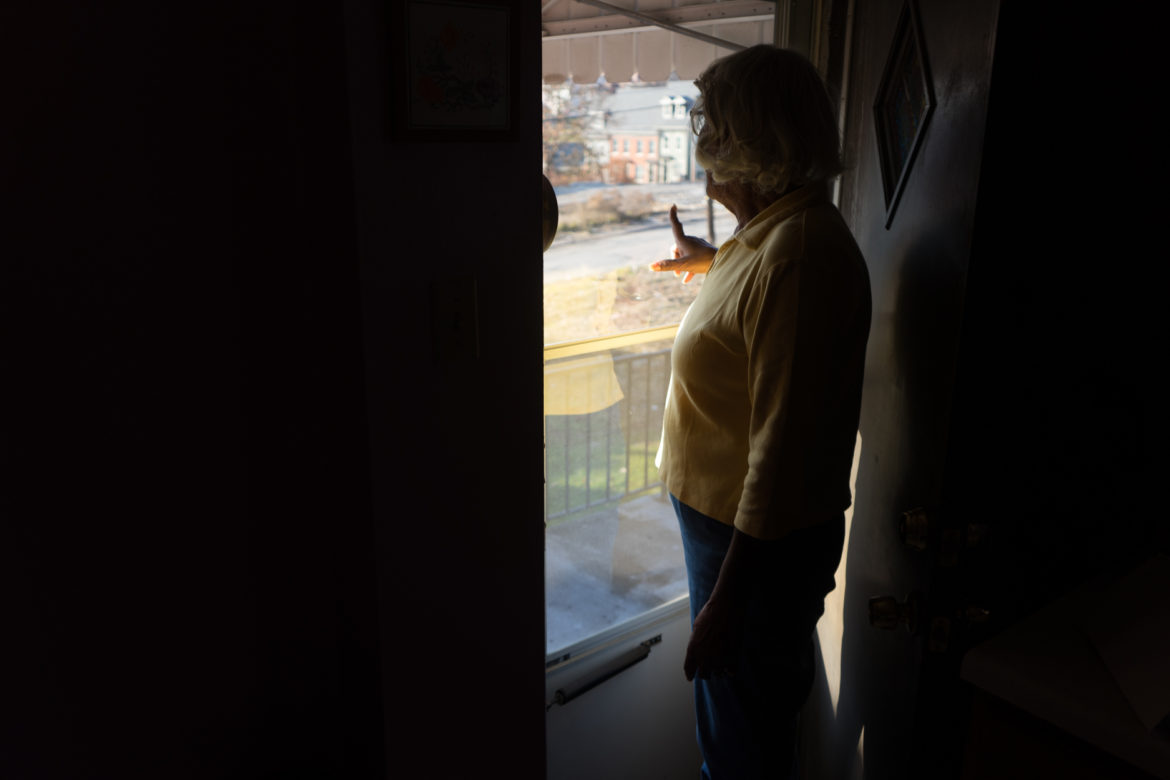 "Arden Ann Harrell explains the changes to the neighborhood from her back door. ""There are blocks and blocks of streets where everything has been torn down,"" she said. (Photo by Aaron Warnick/PublicSource)"