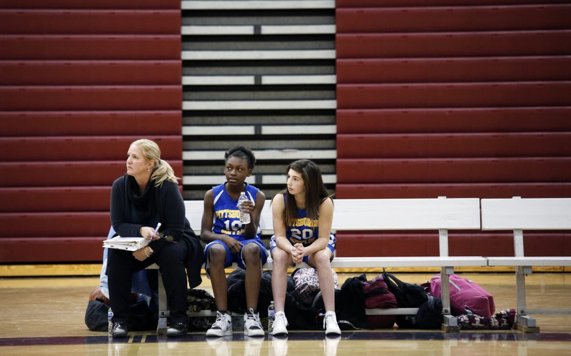 Beth Muehlbauer, coach of the Mifflin PreK-8 middle school girls basketball team, watches from the sidelines with team members Raven Brooks (center) and Isabella Paternoster. The Mifflin team played the middle school team from Obama Academy on Dec. 11, 2017. (Photo by Ryan Loew/PublicSource)