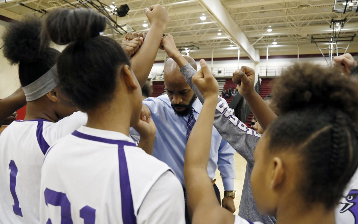 Coach Brice Flenory huddles with members of Obama Academy's middle school girls basketball team before their game against the middle school team from Mifflin PreK-8. (Photo by Ryan Loew/PublicSource)