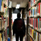 Student walking in between books in library. (Photo by Redd Angelo/ Unsplash)