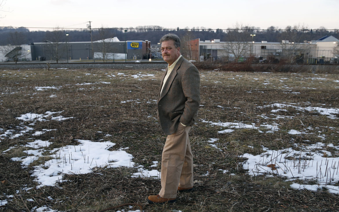 Rick Brennan, Munhall's newly sworn-in mayor, looks out over undeveloped land in the Waterfront area. Brennan said he is committed to the idea of using the space for a public park and will see if, as mayor, he has any power to veto a sale by the borough council. (Photo by Ryan Loew/PublicSource)