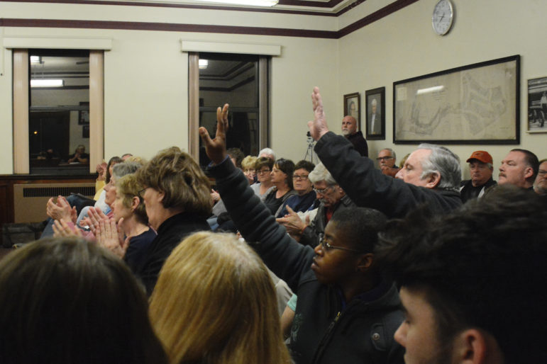 Nearly 50 Munhall residents crammed into the borough's council meeting Tuesday night to hear their elected officials debate the sale of seven acres of land to a private company. Council tabled the bill of sale unanimously. (Photo by Stephen Caruso/PublicSource)