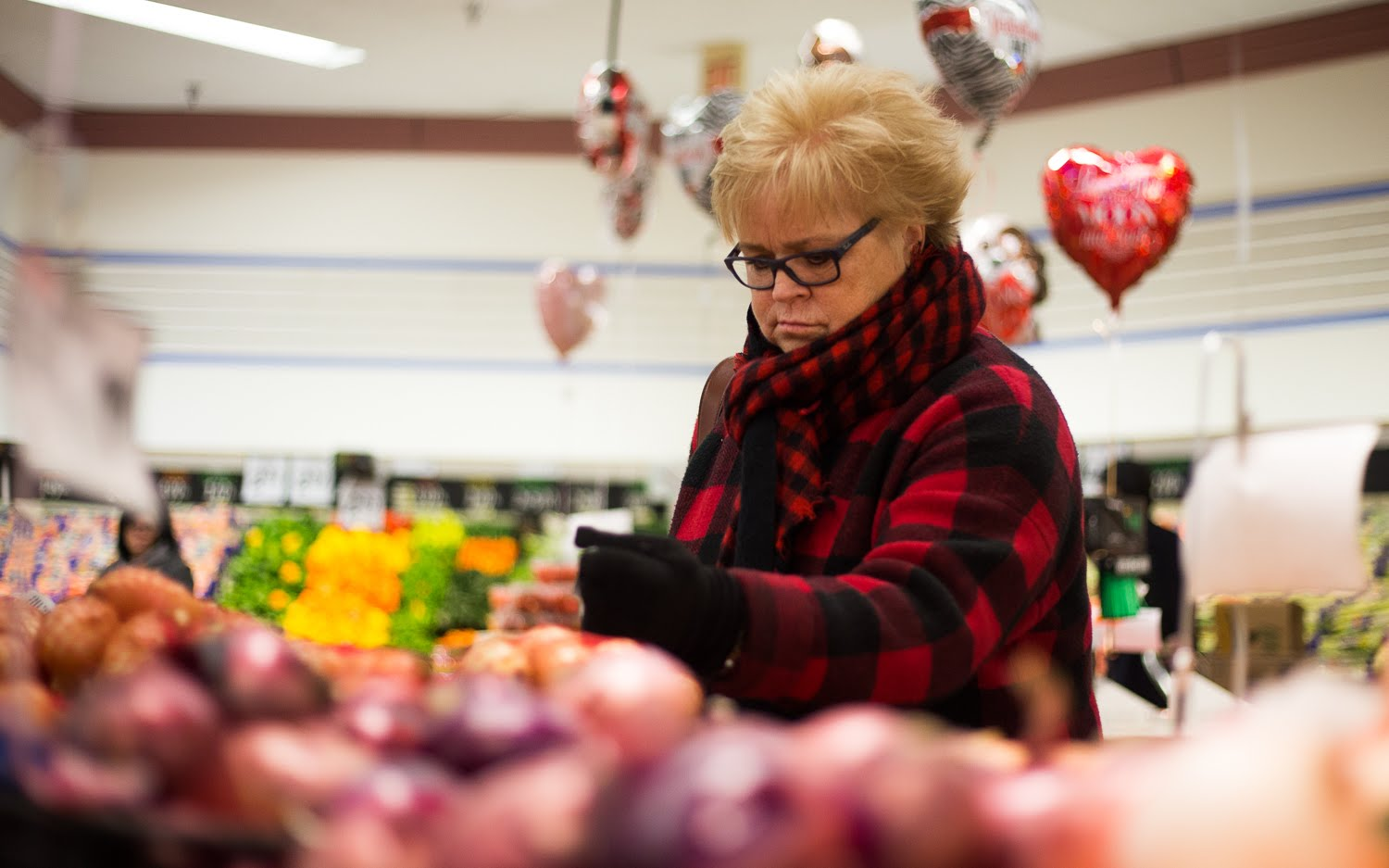 Sandy Kadash looks at a bag of onions in a Washington SHOP 'n SAVE as she buys groceries for an elderly friend. (Photo by John Hamilton/PublicSource)