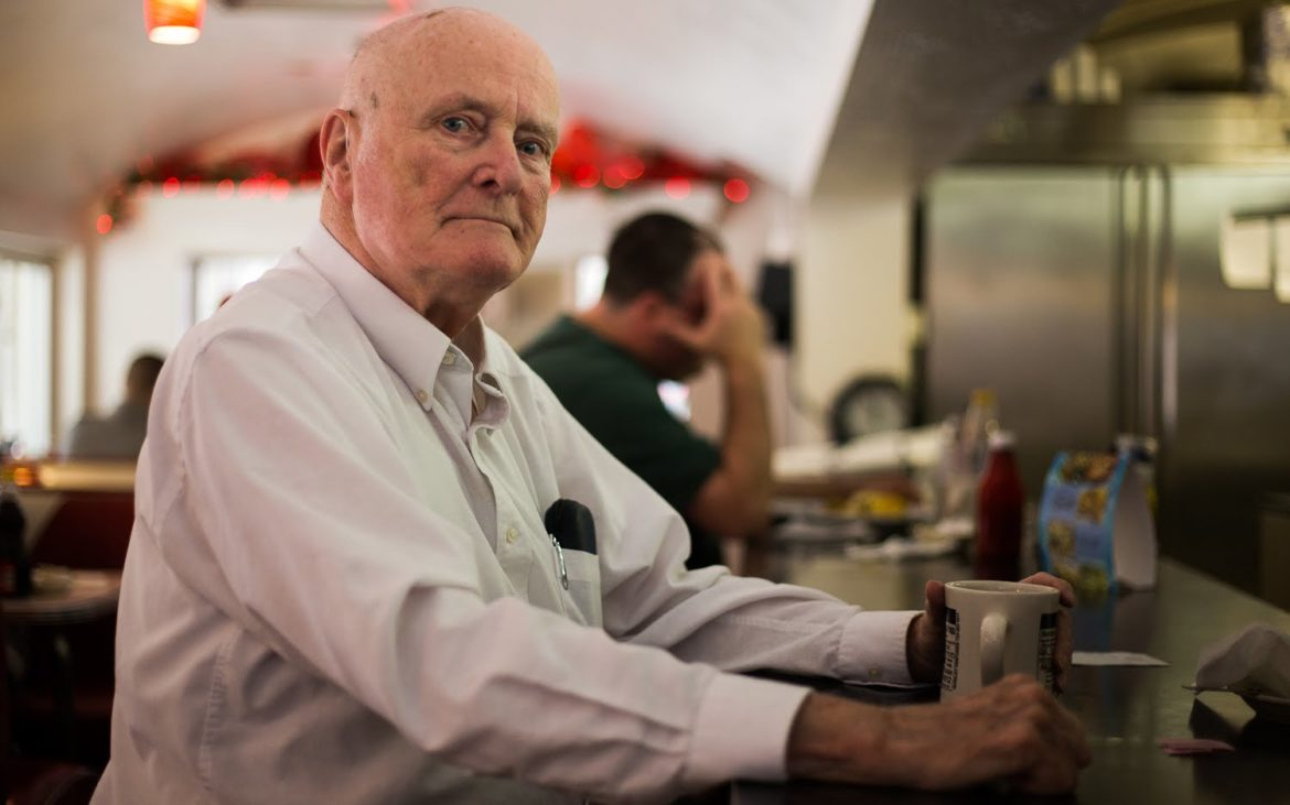 Frank Dallas poses for a portrait at The Diner in Oakdale after finishing his coffee and pastry. (Photo by John Hamilton/PublicSource)