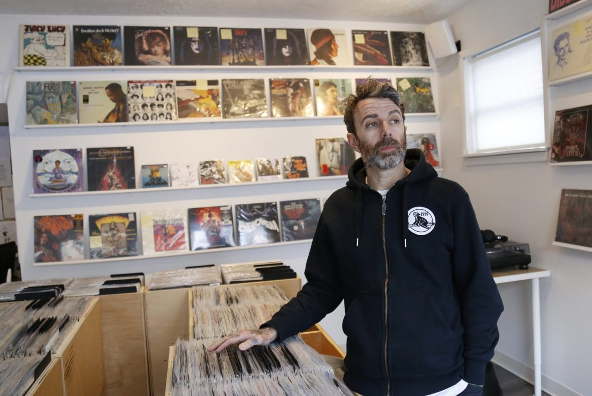 Greg Anderson runs the record store Vinyl Remains on Glenmore Avenue in Dormont. Anderson, who has partnered with the Hollywood Theater on special events, worries what the theater's transition will mean for his and other local businesses. (Photo by Ryan Loew/PubicSource)