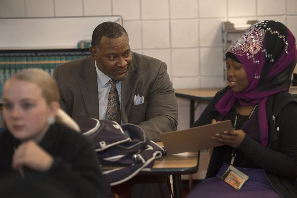 Freshman Majiwa Abdalla shows Dr. Anthony Hamlet a math problem her class is working on at Brashear High School. Seated in front of them is student Angel Schulz. (Photo by Martha Rial/PublicSource)
