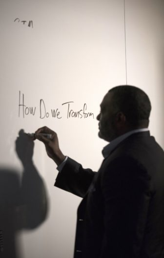 Dr Anthony Hamlet prepares for sending a videotaped messages to staff by writing notes on the board at the Board of Education. (Photo by Martha Rial/PublicSource)