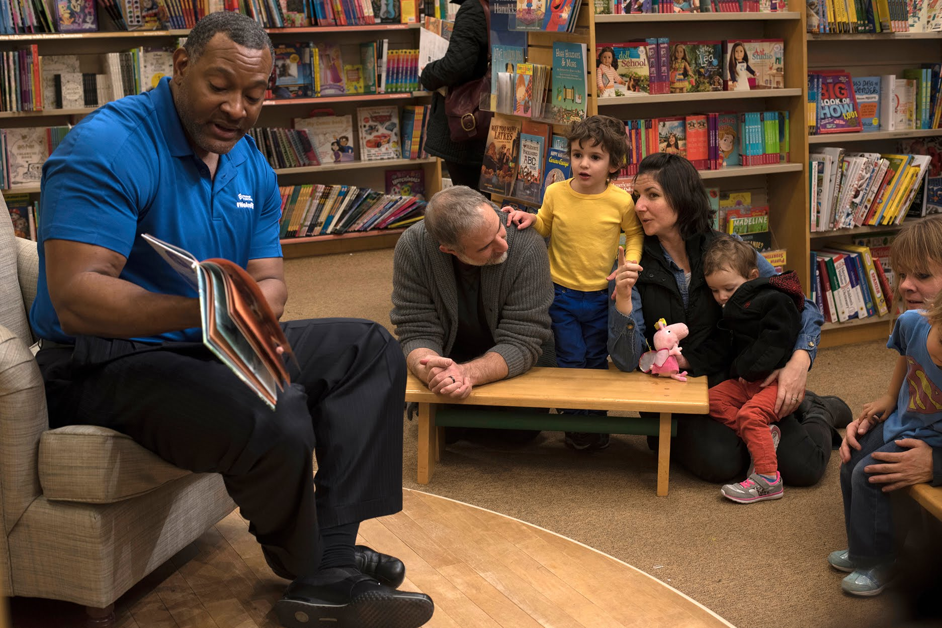 Anna Batista encourages her son Nelson, age 3, to listen Dr. Anthony Hamlet - superintendent of Pittsburgh Public Schools - as he reads to students from Colfax Elementary School at the Barnes & Noble at The Waterfront. Batista is joined by her daughter Alma ands her husband Aaron Batista. (Photo by Martha Rial/PublicSource)