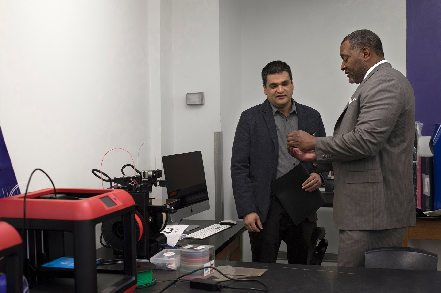 Superintendent Dr Anthony Hamlet inspects an object created by a 3D printer with PTSA president Ashish Badjatia at the grand opening of Google Maker Space at Obama Academy. (Photo by Martha Rial/PublicSource)