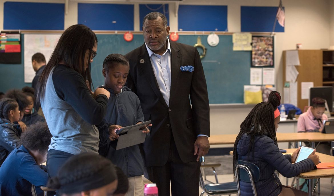 Superintendent Dr Anthony Hamlet observes math teacher Danielle Jackson (left) instructing seventh grader Adai Palmer on the iPad during a visit to Westinghouse High School. (Photo by Martha Rial/PublicSource)