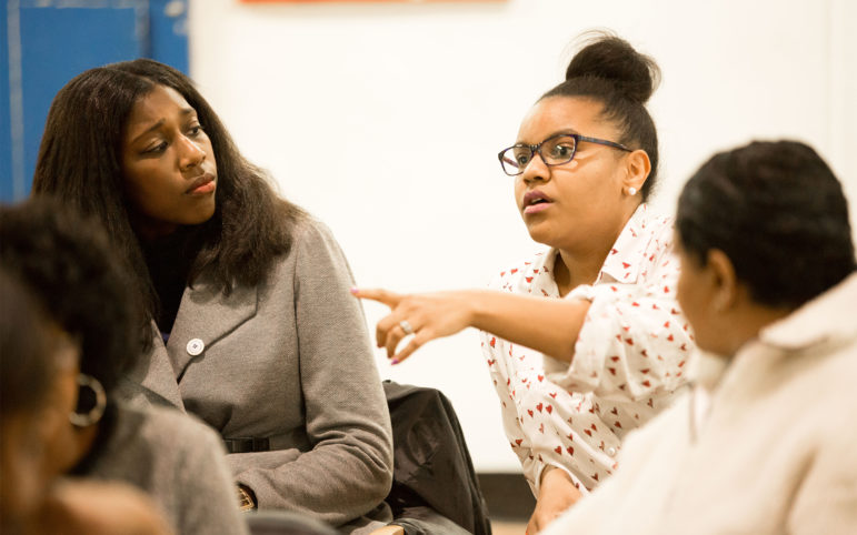 Ashley Comans, a school board director in Wilkinsburg, shares concerns at a community meeting about state legislation that could arm teachers. Wilkinsburg Mayor Marita Garrett, left, opposes the legislation. (Photo by Heather Mull/PublicSource)
