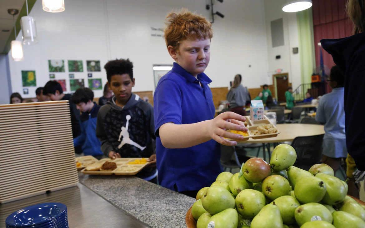 Environmental Charter School sixth grader Miles Hartlage, 12, reaches for a pear in the lunch line at his school on Feb. 6, 2018. (Photo by Ryan Loew/PublicSource)