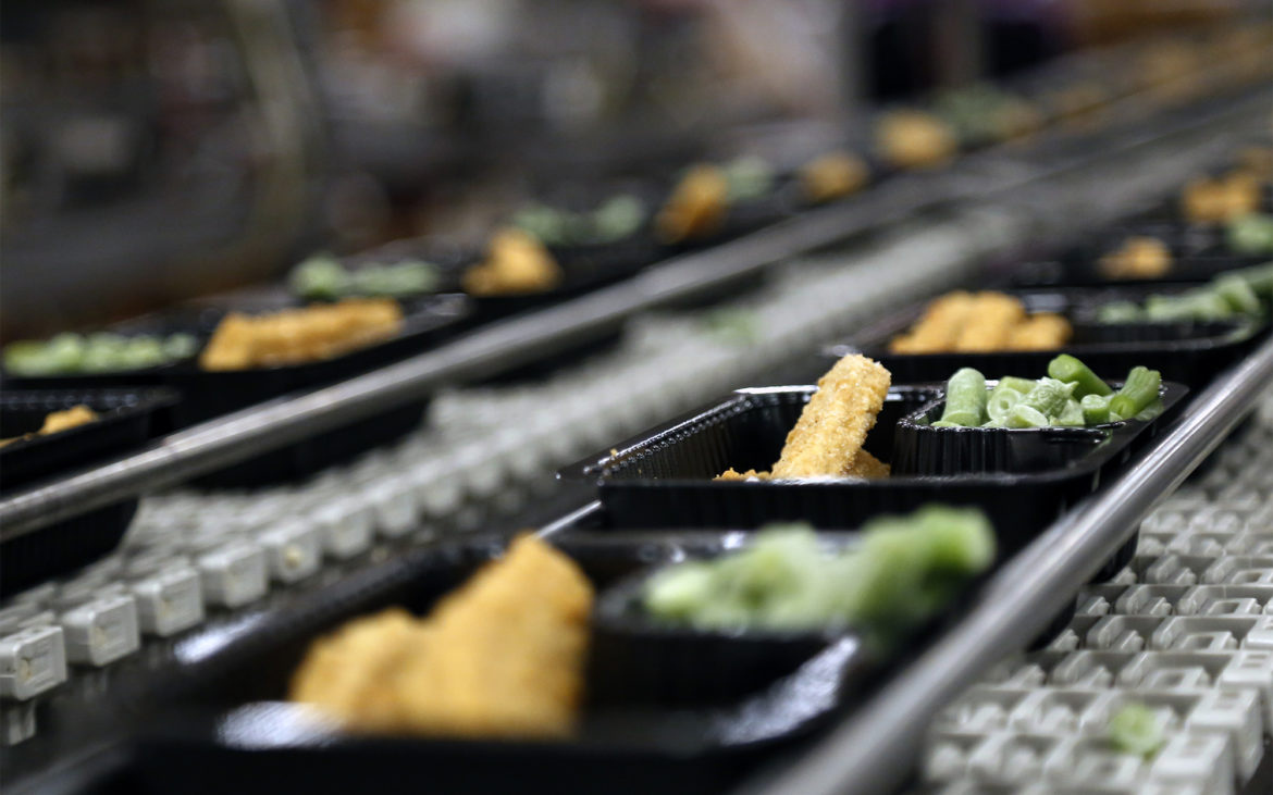 """Hot packs"" with chicken tenders and green beans move along an automated packing line at the Pittsburgh Public Schools food service center on Feb. 20, 2018. On this day, the plan is to make 5,200 packaged meals to be delivered to about 20 schools in the district. (Photo by Ryan Loew/PublicSource)"