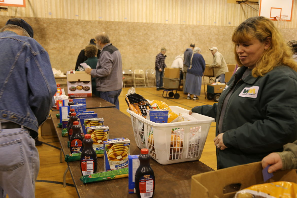 Volunteers assist in distributing mostly shelf-stable items at a food pantry in Fayette County. (Photo by Virginia Alvino Young/90.5 WESA)