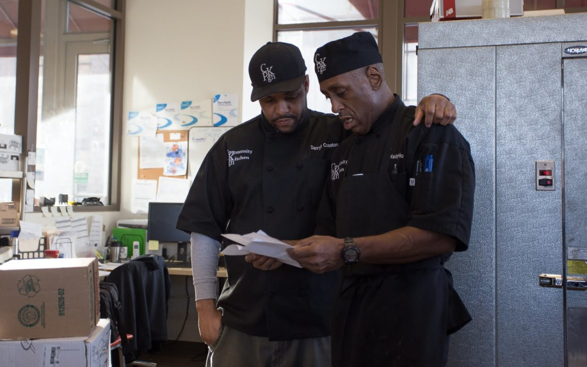 Darryl Coaston, the lead chef trainer at Community Kitchen Pittsburgh, and Keith Holt, a production cook, look at paperwork during morning production on Feb. 13, 2018. (Photo by John Hamilton/PublicSource)